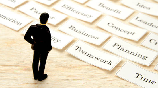 Professional toy figure on table looking at business keywords